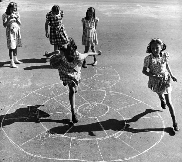 Girls playing hopscotch in the street.